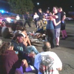 "Police tend to victims outside the Aurora movie theater where a gunman killed 12 and wounded 58 others at a premiere of ""The Dark Knight Rises."""