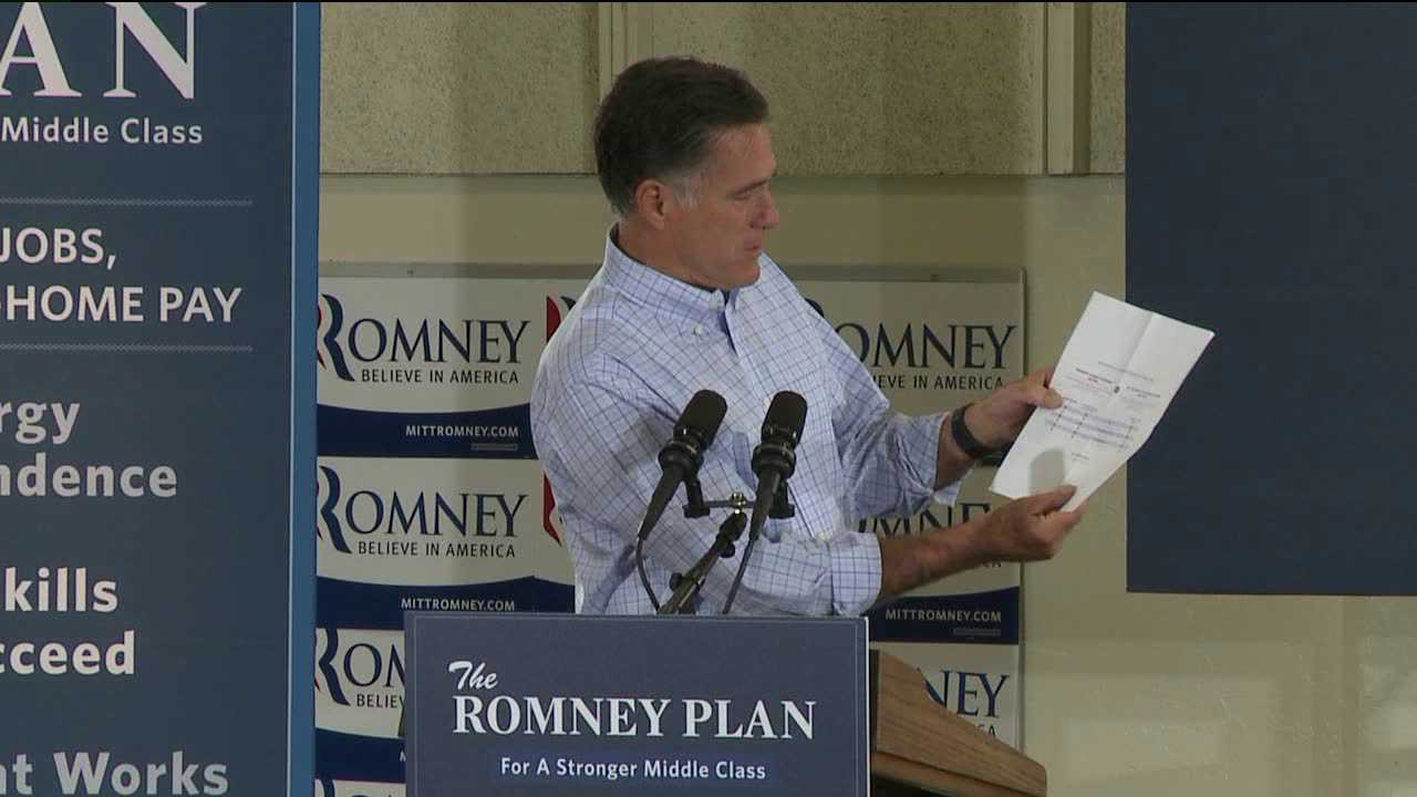 Mitt Romney reviews a report card in Golden on Aug. 2, 2012, that he created for Barack Obama. He said the President failed