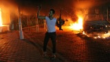 A man waves his rifle as buildings and cars are engulfed in flames inside the U.S. Consulate compound in Benghazi, Libya, late on Tuesday, September 11
