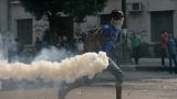 An Egyptian protester throws a tear gas canister at riot police Thursday during clashes near the U.S. Embassy in Cairo