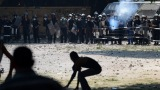 An Egyptian riot police officer fires tear gas toward protesters during clashes Thursday with police near the U.S
