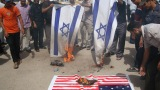 Iraqi protesters burn Israeli and U.S. flags during a protest Thursday, September 13, denouncing a film deemed offensive to Islam
