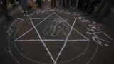 People stand around a drawing that says 'Remember your black day 11 September' during the protest in Cairo