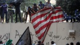 Protesters pull down a U.S. flag