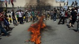 Yemeni protesters gather around a fire Thursday during a demonstration outside the U.S. Embassy in the capital of Sanaa. Yemeni forces fired warning shots to disperse the thousands of protesters