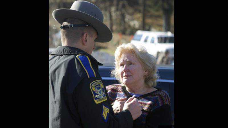 A woman speaks with a Connecticut state trooper outside Sandy Hook Elementary School on Dec. 14, 2012. (Photo: CNN)