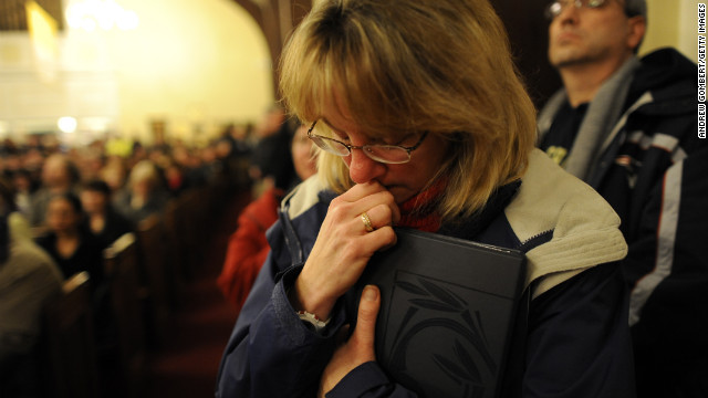 A woman bows her head during a vigil for the shooting victims on December 14 (Photo: CNN)
