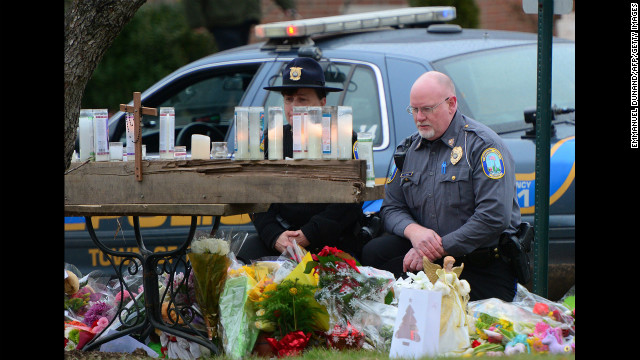 Police officers honor the victims of the school shooting at the St. Rose of Lima Roman Catholic Church on December 16 in Newtown (CNN)