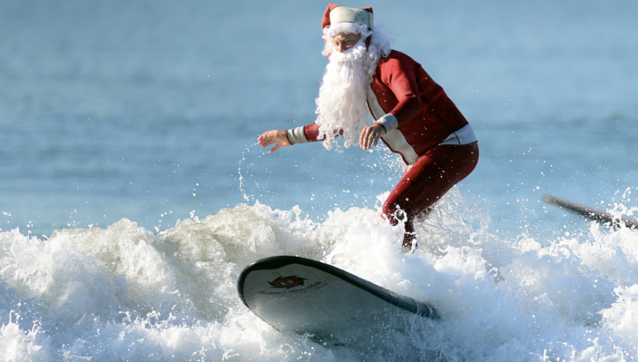 Michael Pless, 62, catches a wave off Seal Beach, south of Los Angeles, on Friday, December 21, in California. Pless, who also runs a surfing school, has been dressing up as Santa Claus and taking to the waves in costume since the 1990s, sometimes joined by his wife, Jill, in a Michael Pless, 62, catches a wave off Seal Beach, south of Los Angeles, on Friday, December 21, in California. Pless, who also runs a surfing school, has been dressing up as Santa Claus and taking to the waves in costume since the 1990s, sometimes joined by his wife, Jill, in a Mrs. Claus outfit. (Photo: CNN). Claus outfit.
