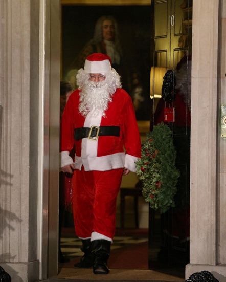Santa Claus walks out of the front door during a Christmas party hosted for sick children at 10 Downing Street on Monday, December 17, in London. (Photo: CNN)