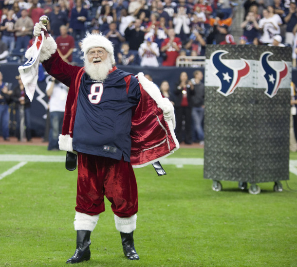Santa Claus opens his coat to reveal a Matt Schaub jersey at Reliant Stadium on Sunday, December 16, in Houston, Texas, before the Texas Longhorns played the Indianapolis Colts. (Photo: CNN)