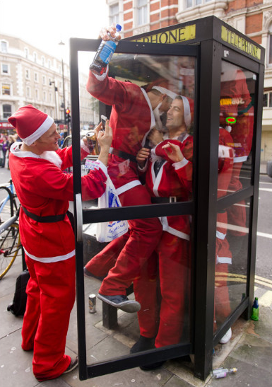 Costumed Santas crowd into a telephone booth during the Santacon pub crawl near London's Trafalgar Square on December 15. (Photo: CNN)