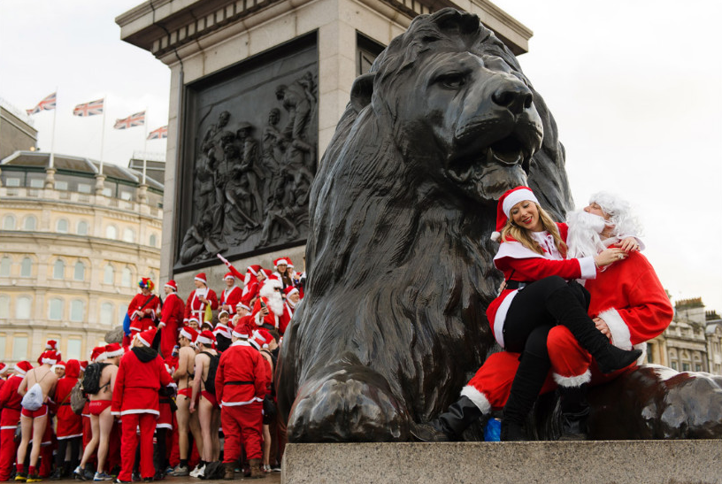 Revelers in Santa costumes sit on the lion statue at the base of Nelson's Column in London's Trafalgar Square on December 15. (Photo: CNN)