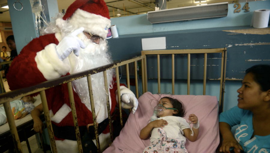 A man dressed as Santa Claus sees a patient in the pediatric ward of a hospital in Guatemala City, Guatemala, on Friday, December 14. (Photo: CNN)