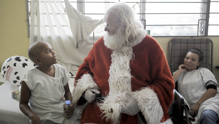 Icelandic philantropist Einar Sveinsson, dressed as Santa Claus, speaks with a patient in the oncology ward during a visit to the Benjamin Bloom National Children's Hospital in San Salvador, El Salvador, on Tuesday, December 11. (Photo)