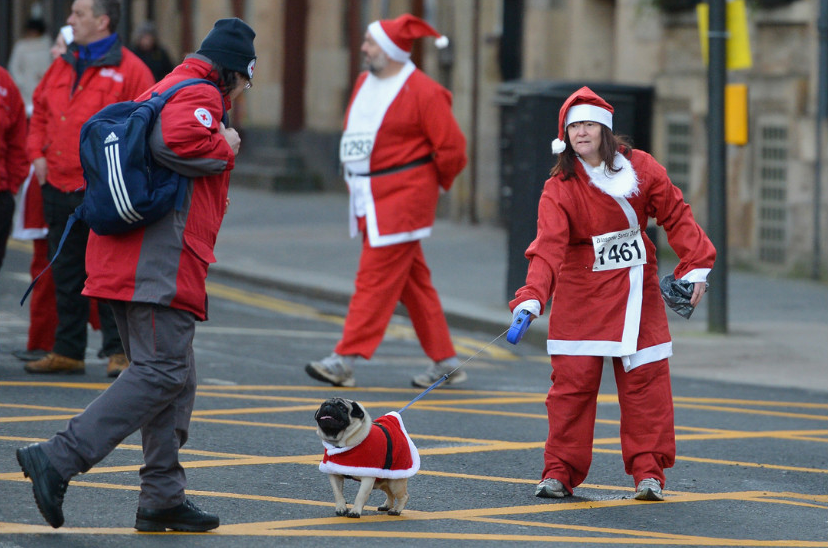A woman and her dog in Santa suits prepare for the annual Glasgow Santa Dash on December 9 in Glasgow, Scotland. (Photo: CNN)
