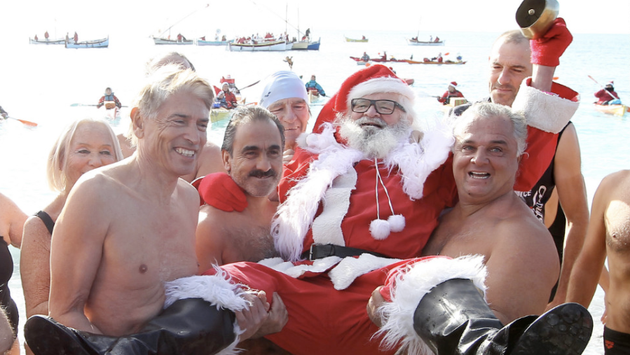 Beachgoers carry a man wearing a Santa Claus costume on the Mediterranean coast on Saturday, December 8, in Nice, France. (Photo: CNN)