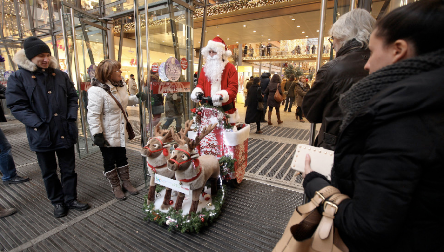 A customer holds the door of a shopping mall for a man dressed as Santa Claus on December 8, in Berlin. (Photo: CNN)