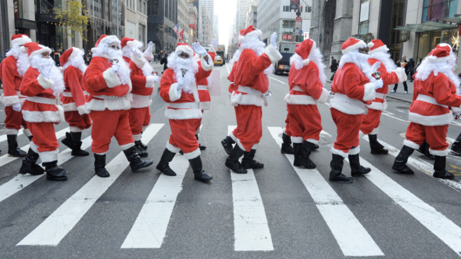Volunteers in New York's 110th annual Sidewalk Santa Parade cross the street on Friday, November 23. (Photo: CNN)