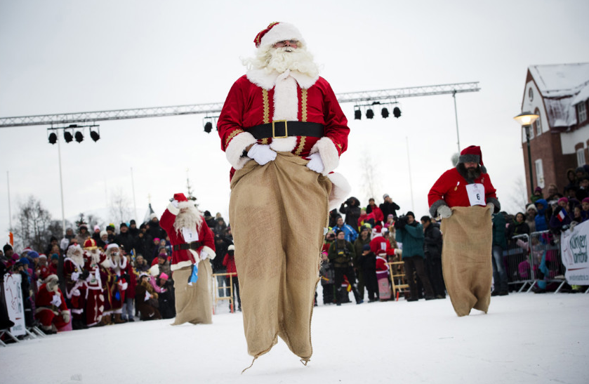 "Estonian Santa Claus ""Santa Aare,"" from left, Dutch Santa Claus ""Santa Holland"" and Swedish Santa Claus ""Snaretomten"" compete in the Kicksled Sack Race during the Santa Claus Winter Games in Gallivare, Sweden, on Saturday, November 17. (Photo: CNN)"