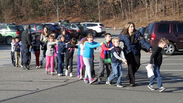 State police personnel lead children away from Sandy Hook Elementary School in Newtown, Conn., following a shooting on Dec. 14, 2012. (Photo: Shannon Hicks/The Newtown Bee)