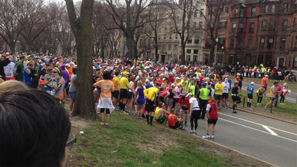 Boston Marathon runners gather after two explosions took place near the finish line on April 15, 2013. (Photo: Twitter)