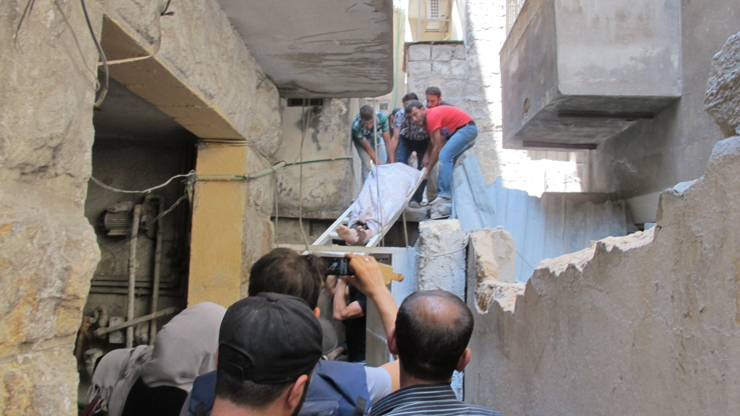 Residents of Aleppo, Syria carry the body a man shot dead by a sniper in front of his house. (Credit: CNN)
