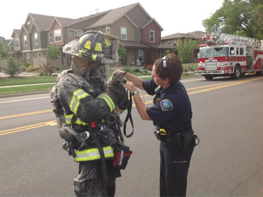 Police aids firefighter in pet rescue.(Credit: Boulder Police)