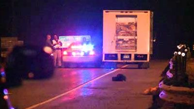 Police investigate at the scene of an accident involving a delivery truck and a pedestrian that left one dead on the morning of June 3, 2013.