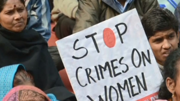 A protester holds up a sign after a rash of rape in India. (Photo: CNN)