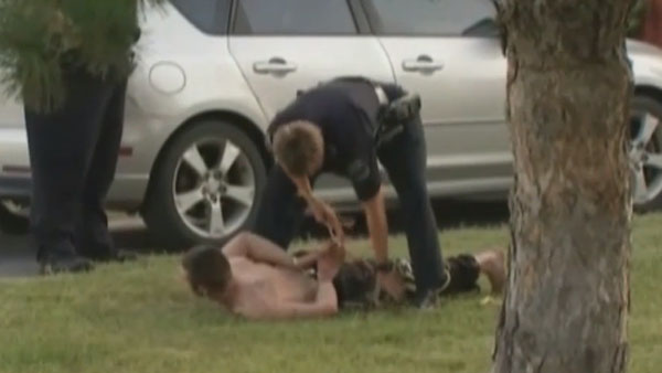 A police officer works to free Oklahoma burglary suspect Robert Cole after he was hogtied by a homeowner on July 3, 2013. (Photo: FoxNews.com)