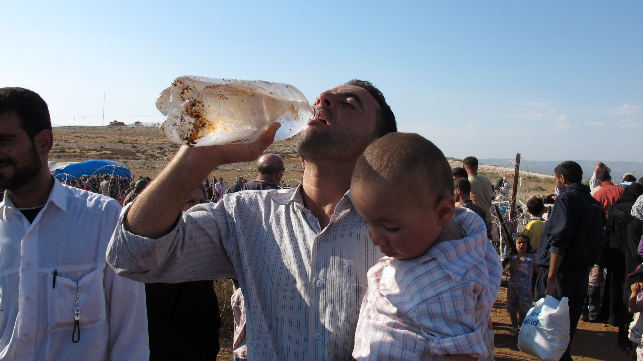 A Syrian refugee with his baby boy in his arms pauses to take a drink of water in northern Syria. (Credit: CNN)