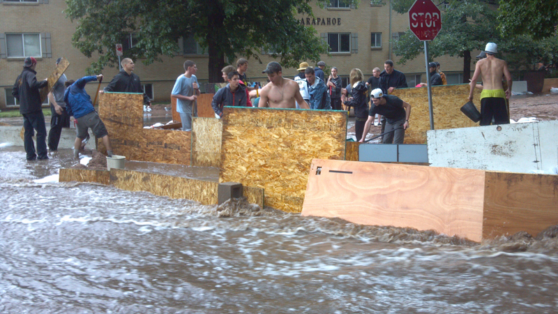 Boulder residents work to board up an intersection against rising flood waters on Sept. 12, 2013.
