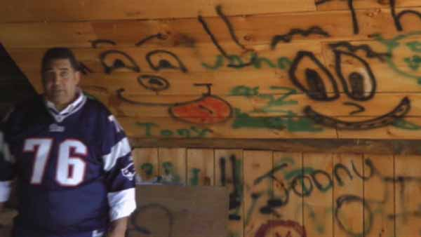 Former NFL offensive lineman Brian Holloway stands in front of a graffitied wall in his rural vacation home in Stephentown, New York, that was trashed during a Labor Day weekend party attended by about 300 teenagers. (Photo: HelpMeSave300.com)