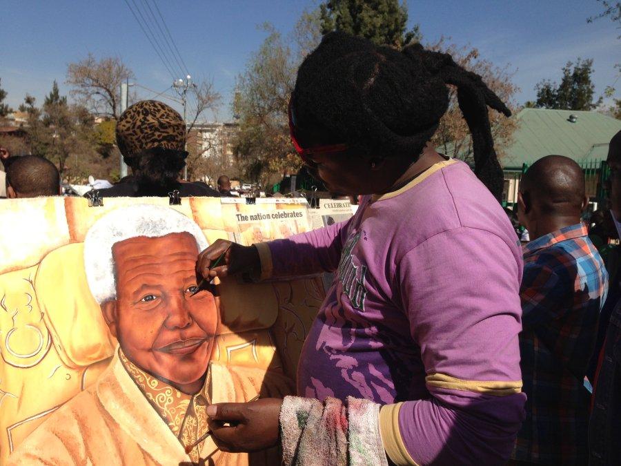 An artist paints a portrait of Nelson Mandela outside the hospital where he has been since June 8.