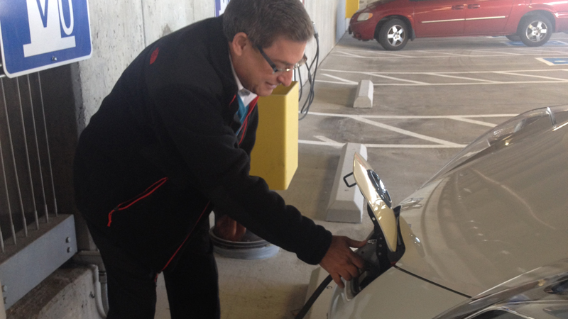 Paul Rosenberg, vice president of membership development for the Aurora Chamber of Commerce, charging his electric vehicle at the city of Aurora's new electric vehicle charging stations.