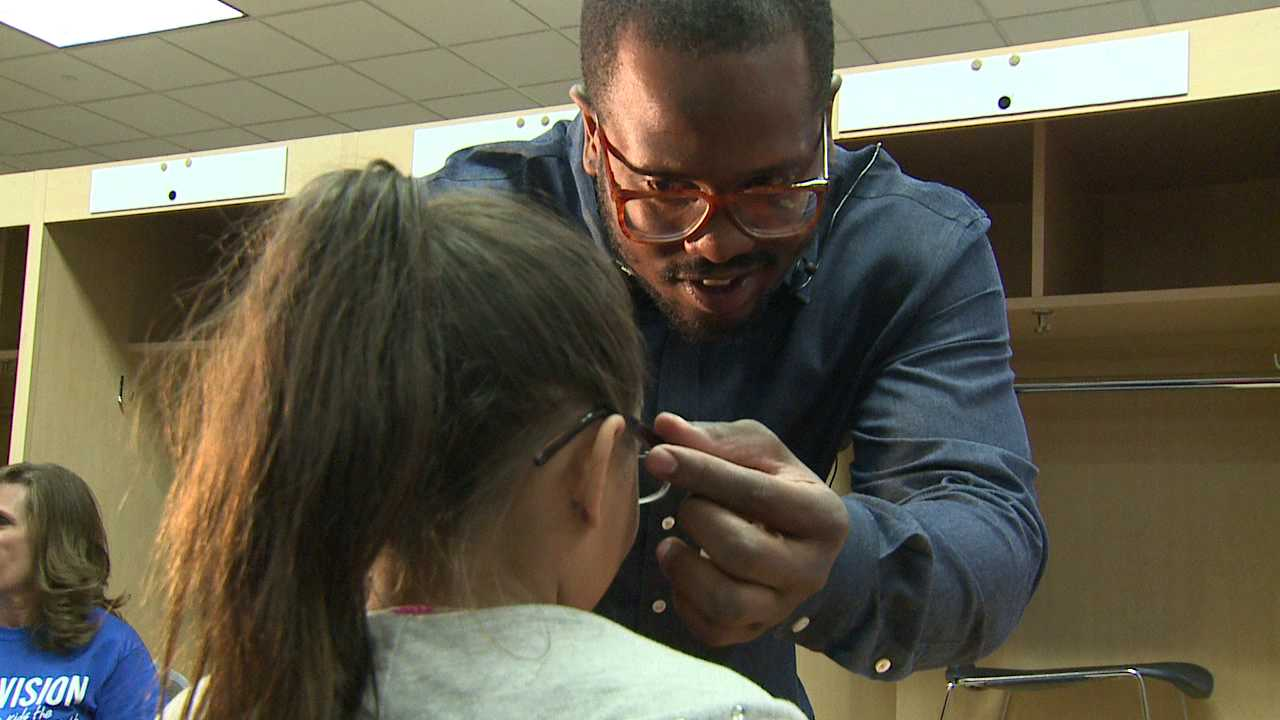 Broncos player Von Miller helps a girl with her new glasses