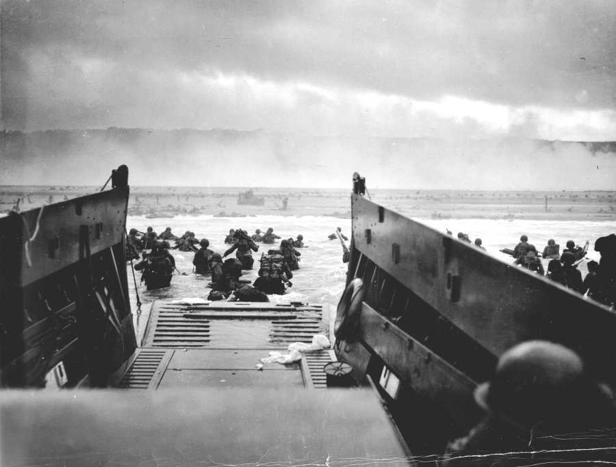 A photo by CPHOM Robert F. Sargent, USCG. A Coast Guard-manned LCVP from the U.S.S. Samuel Chase disembarks troops of Company E, 16th Infantry, 1st Infantry Division on the morning of 6 June 1944 at Omaha Beach.
