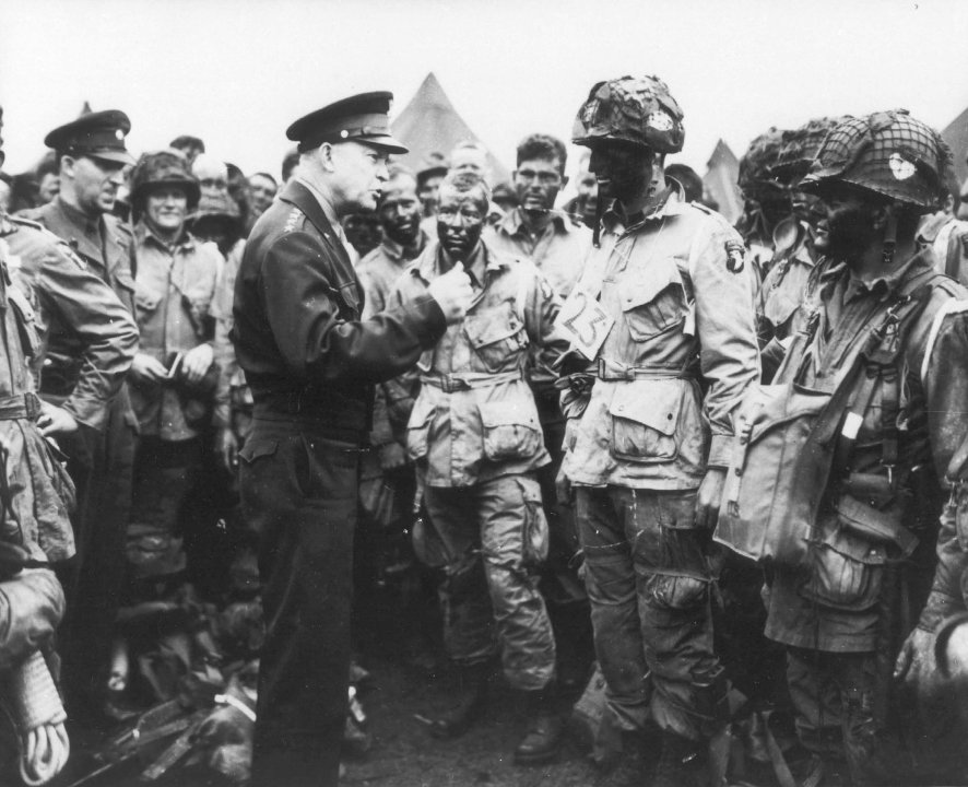 """General Dwight D. Eisenhower gives the order of the Day. """"Full victory-nothing else"""" to paratroopers in England, just before they board their airplanes to participate in the first assault in the invasion of the continent of Europe."""