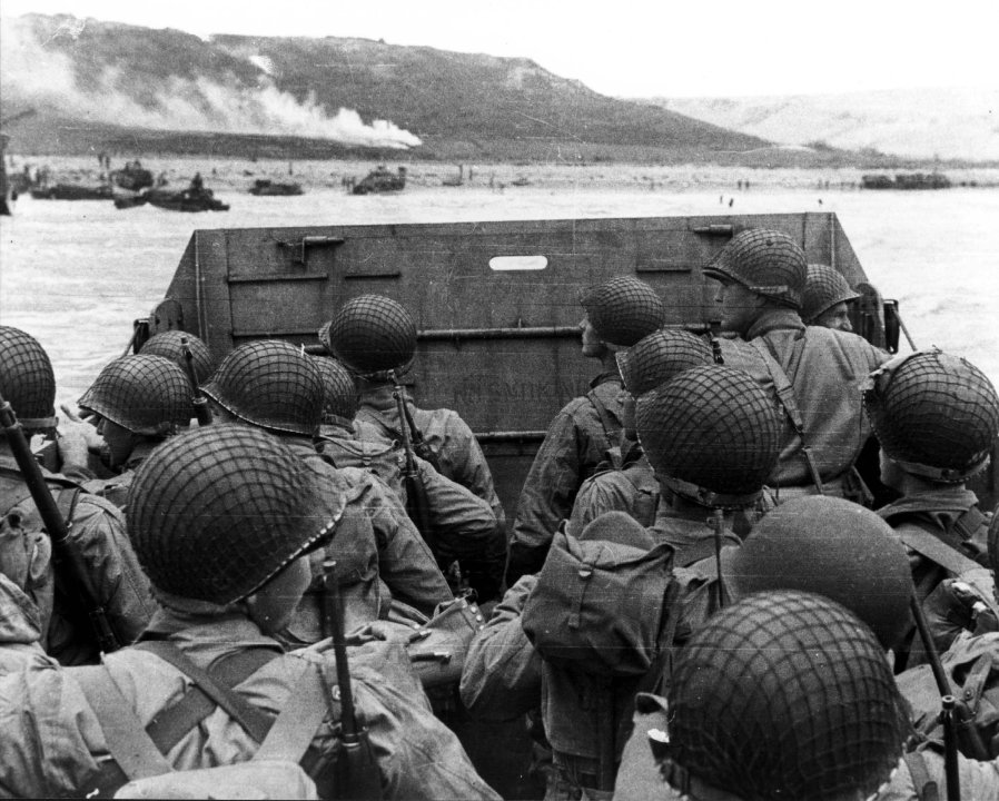 """American assault troops in a landing craft huddle behind the protective front of the craft as it nears a beachhead, on the Northern Coast of France on June 6, 1944. Smoke in the background is Naval gunfire supporting the land. Note faint """"No Smoking"""" sign on the LCVP's ramp; and M1903 rifles and M1 carbines carried by some of these men."""