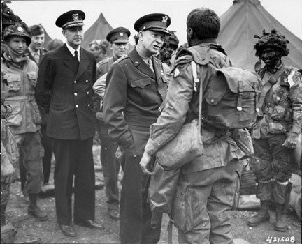 """General Dwight D. Eisenhower gives the order of the day. """"Full victory-nothing else"""" to paratroopers in England, just before they board their airplanes to participate in the first assault in the invasion of the continent of Europe. From: Dwight D. Eisenhower Presidential Library and Museum"""