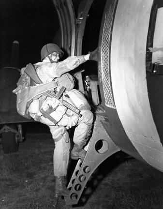 A paratrooper loads for take off in England in preparation to leave for the liberation of Europe from the Nazis on June 6, 2012. Full source: Dwight D. Eisenhower Presidential Library and Museum