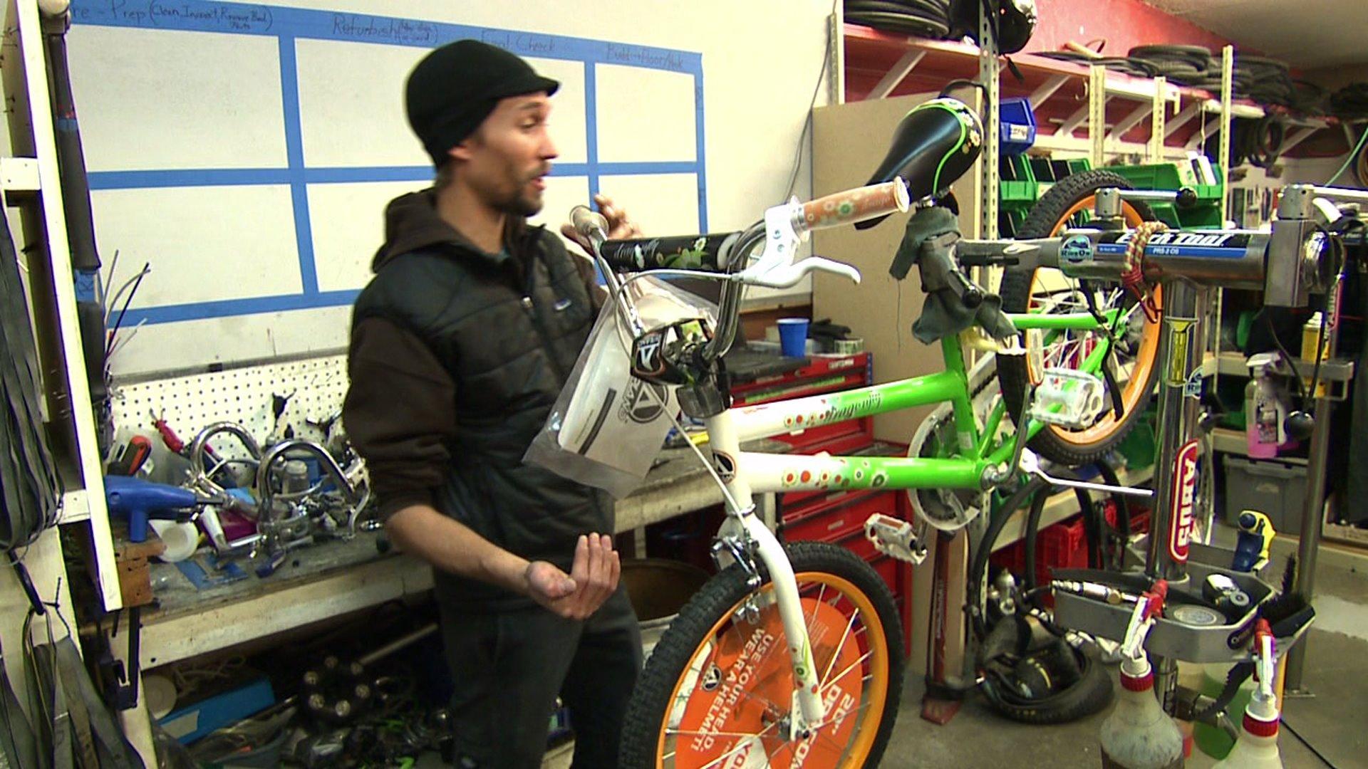 Bike expert Jordyn Dratyon inspects a child's bicycle