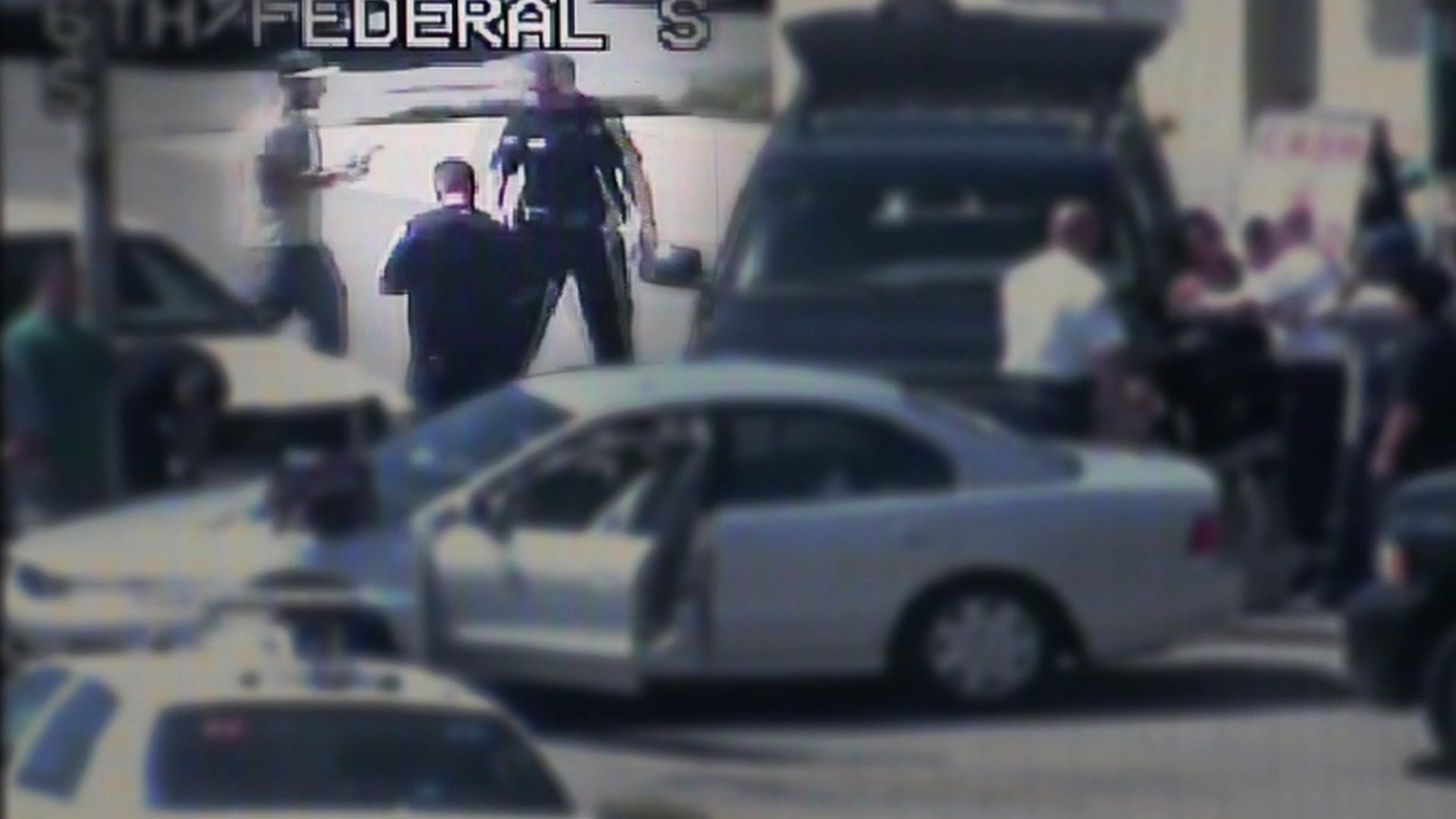 Levi Fraiser, highlighted in the upper left, carries his tablet to a Denver police SUV in this HALO camera image