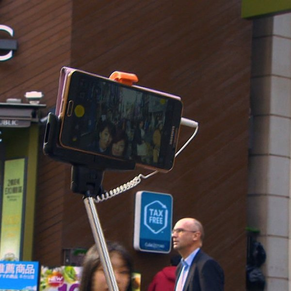 A couple in Hong Kong uses a selfie stick, a long pole used to extend their camera phone more than three feet away allowing a wide frame for the photograph.