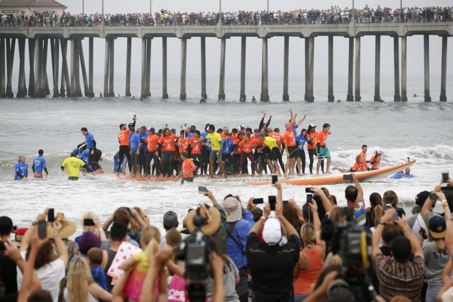 Sixty-six surfers climbed onto a giant surfboard Saturday in Huntington Beach, California, and rode it into the record books. The surfers came together on International Surf Day, held annually on the summer solstice, to beat the record of 47 people riding a board in Australia in 2005. (Photo: CNN)