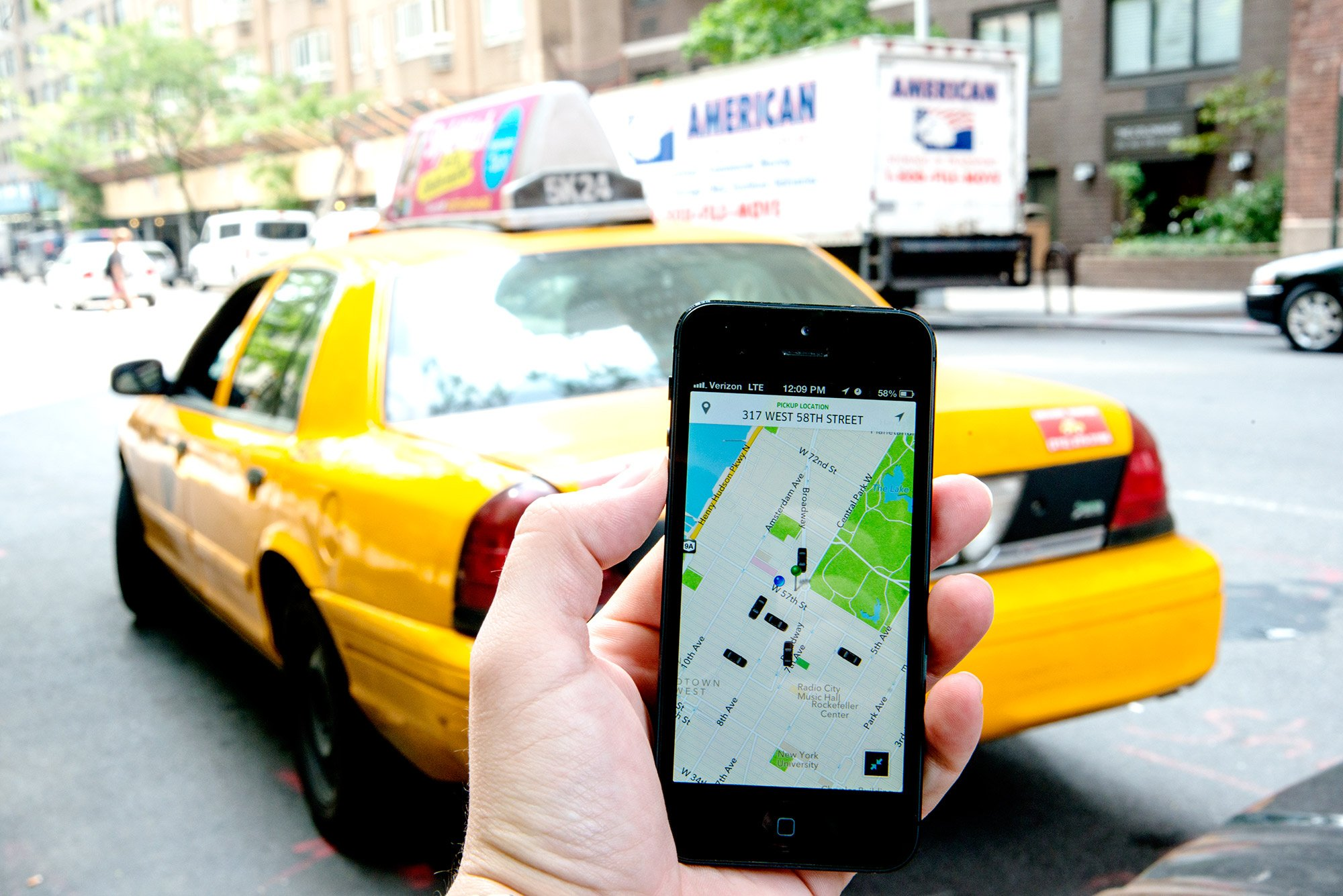 Uber, a ride sharing service, as seen through their iOS app near Central Park, New York, New York. A taxi is seen in the background. (Photo: CNN)