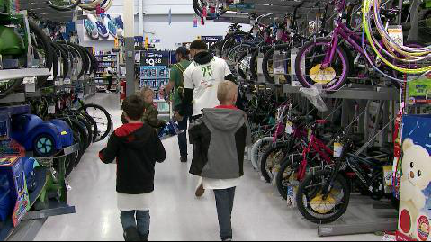 Denver Broncos players and children walk the bicycle aisle while shopping
