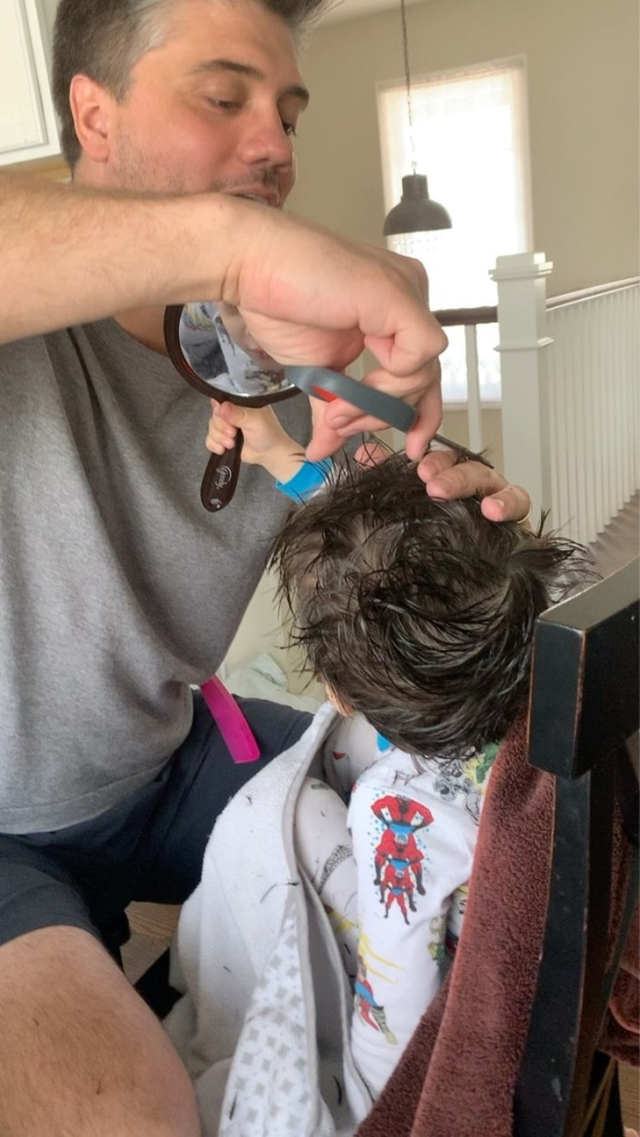 Otto Boone getting a haircut from his dad