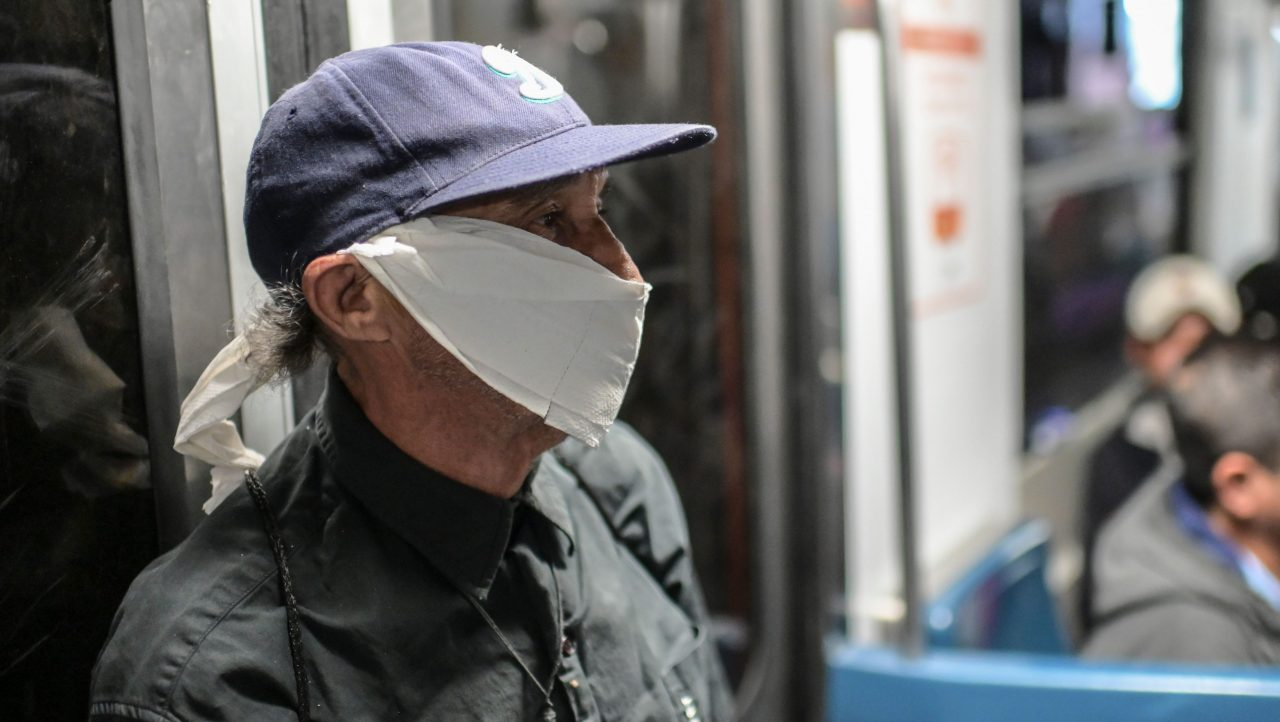 A man wearing a paper-face mask travels on the subway in Mexico City, on April 2, 2020.